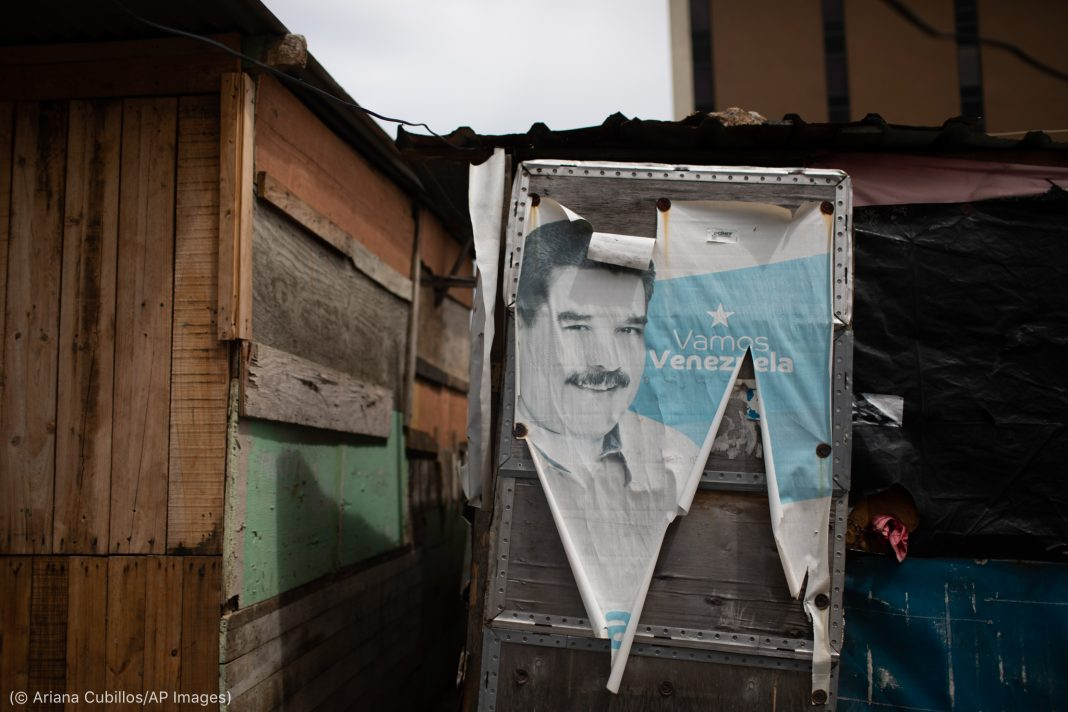 Torn and faded Nicolás Maduro campaign poster covering shack's door (© Ariana Cubillos/AP Images)