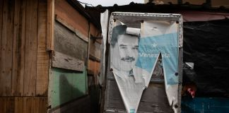 Torn and faded Nicolas Maduro campaign poster covering the door of a shack home (© Ariana Cubillos/AP Images)