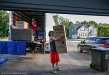 Pria membawa kotak besar dari truk ke garasi (© John Minchillo/AP Images)