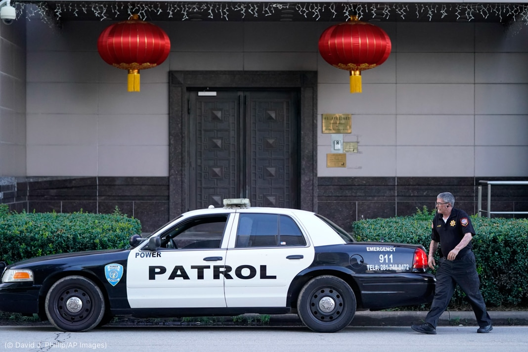 Security guard walking next to patrol car outside building with two red lanterns and double door (© David J. Phillip/AP Images)