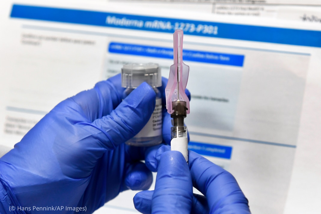 Gloved hands holding vial and hypodermic needle (© Hans Pennink/AP Images)