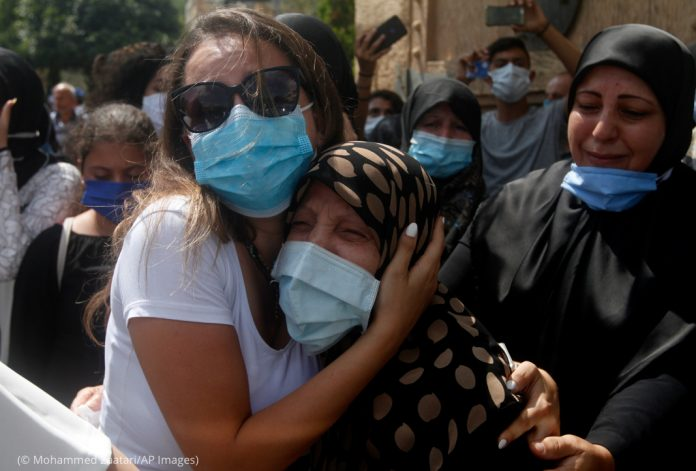 Two women holding each other as they mourn a victim of the Beirut explosion (© Mohammed Zaatari/AP Images)