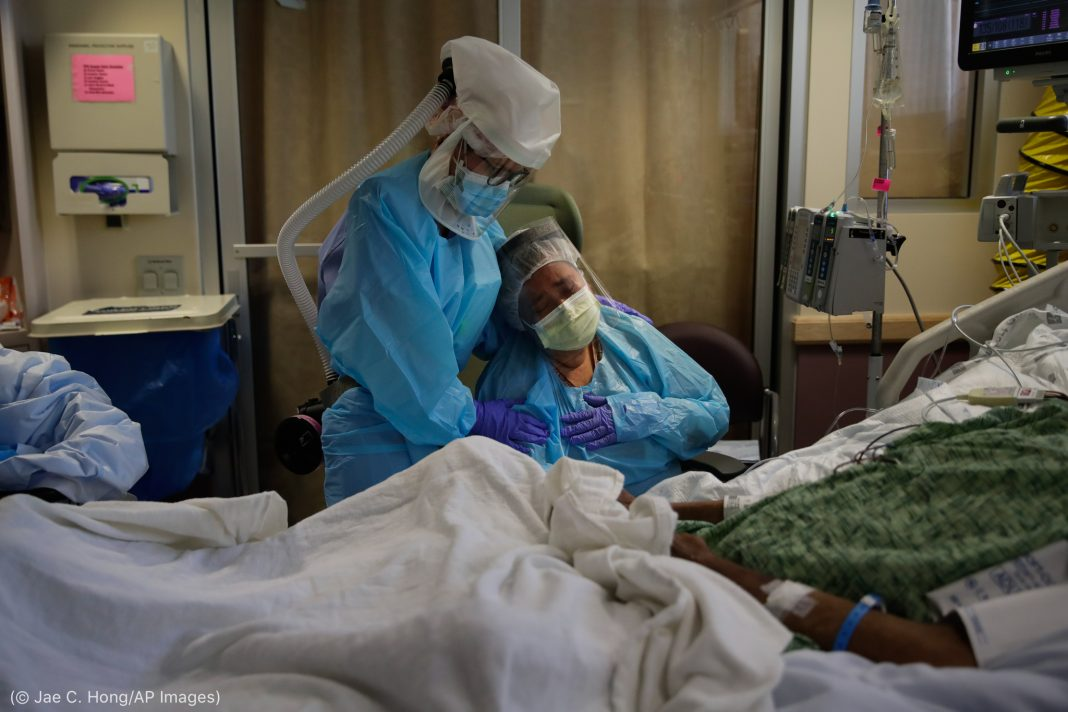 Nurse wearing protective equipment comforting woman next to patient in hospital bed (© Jae C. Hong/AP Images)