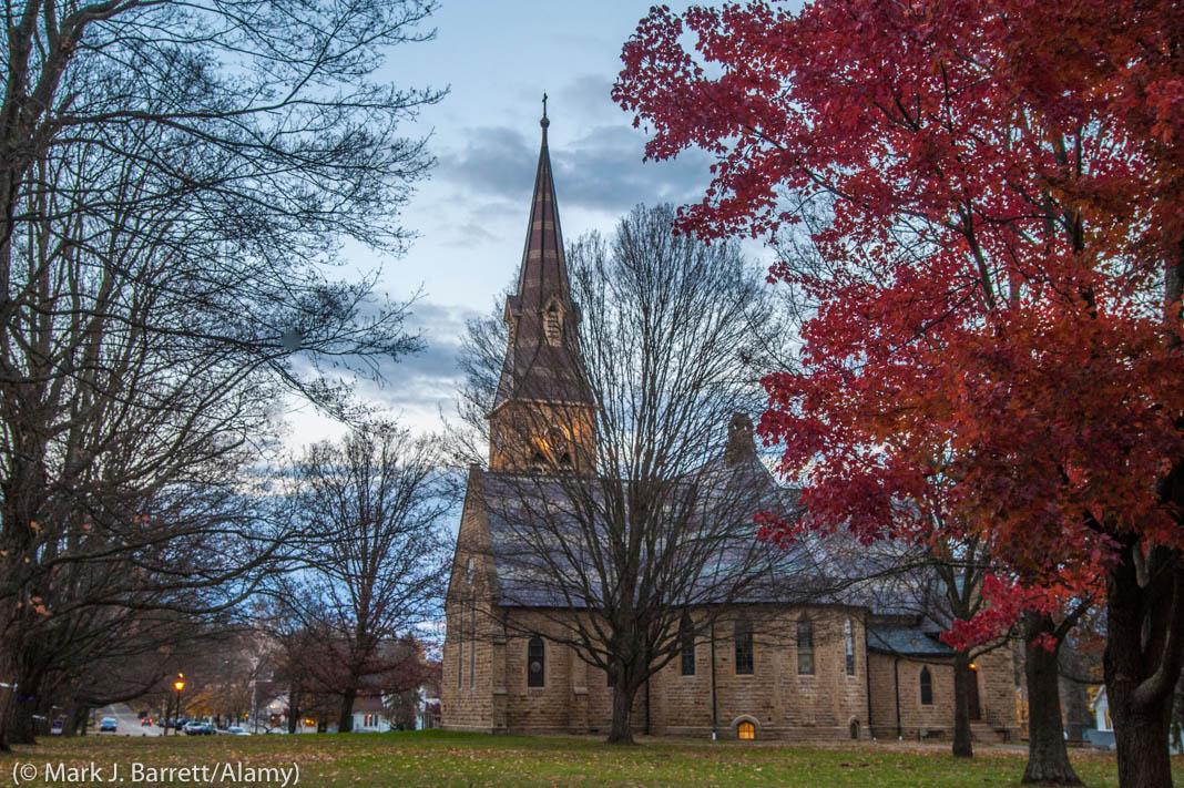 Árboles que rodean una torre con un reloj y a una iglesia (© Mark J. Barrett/Alamy)