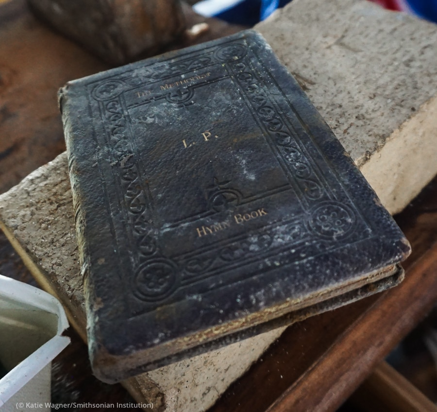 Old, worn moisture-damaged book with stains on its tooled cover (© Katie Wagner/Smithsonian Institution)