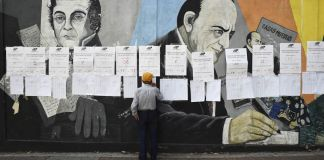 Man looking at paper tacked to a colorful mural (© Yuri Cortez/AFP/Getty Images)