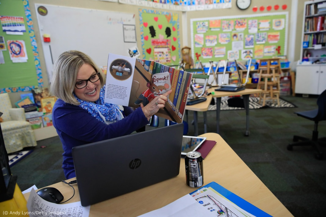 Woman holding and pointing at book in front of laptop computer in classroom (© Andy Lyons/Getty Images)