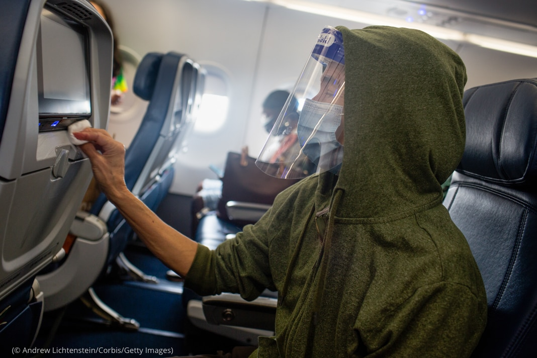 Passenger seated in airplane row, wearing mask and face shield, wiping seatback in front of him (© Andrew Lichtenstein/Corbis/Getty Images)