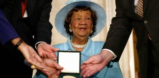 Dorothy Height sitting and receiving medal in case while surrounded by people (© Stephen Jaffe/AFP/Getty Images)