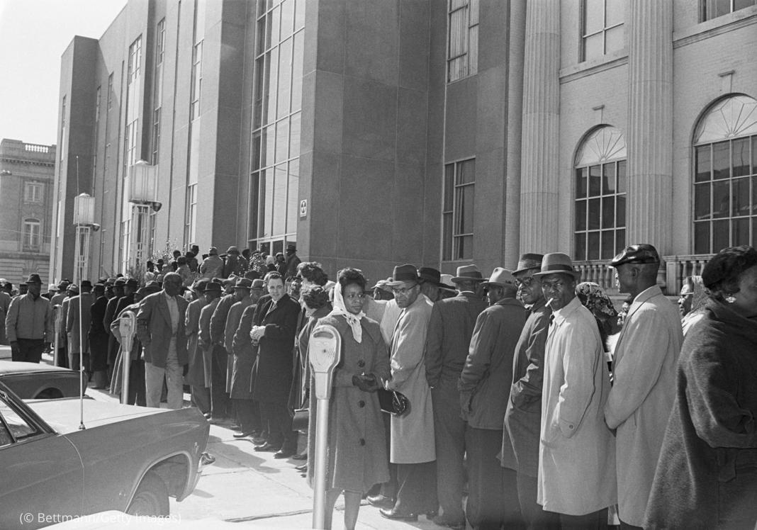 People standing in long line on downtown sidewalk (© Bettmann/Getty Images)