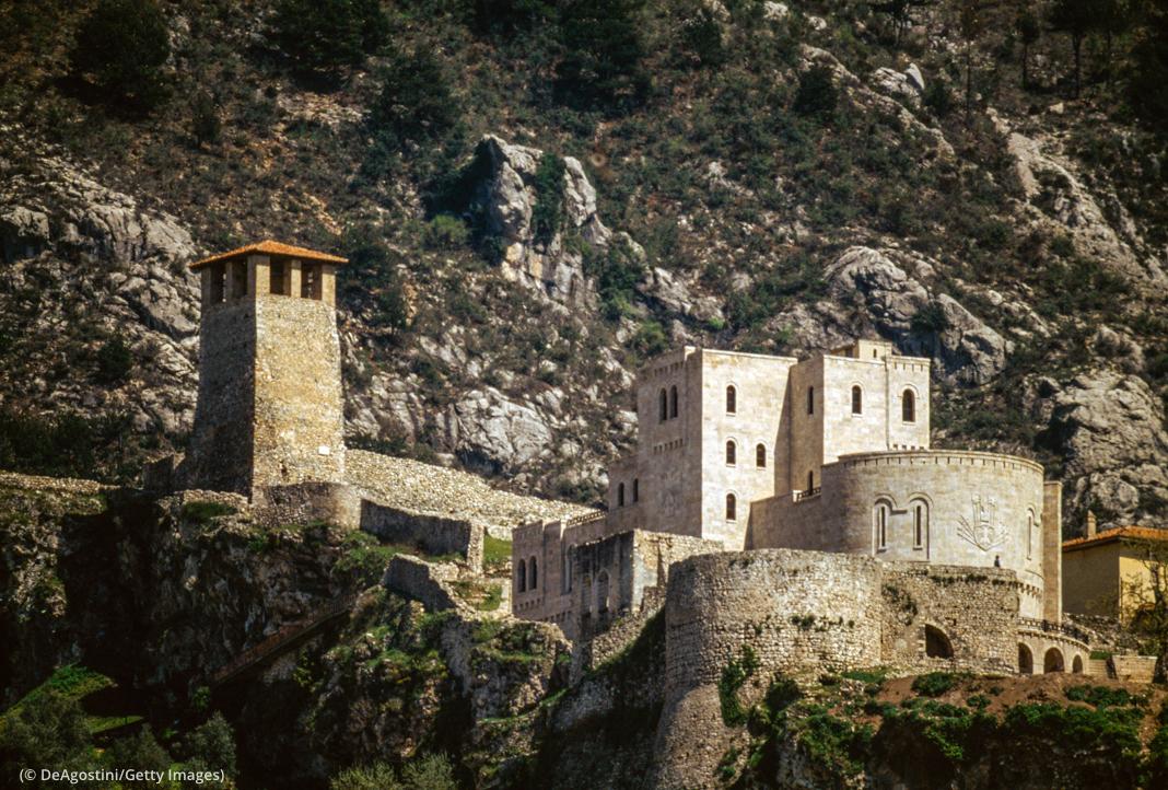 Des montagnes entourant un bâtiment historique avec des tours et des murailles (© DeAgostini/Getty Images)
