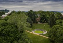 Aerial view of circular memorial on tree-filled campus with mountains in background (© Sanjay Michael Suchak/UVA Today)