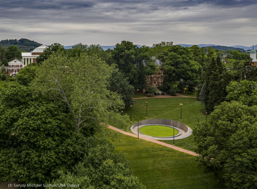 پس منظر میں دکھائی دینے والے پہاڑوں اور درختوں میں گھرے کیمپس پر واقع ایک گول یادگار کا فضائی منظر (© Sanjay Michael Suchak/UVA Today)