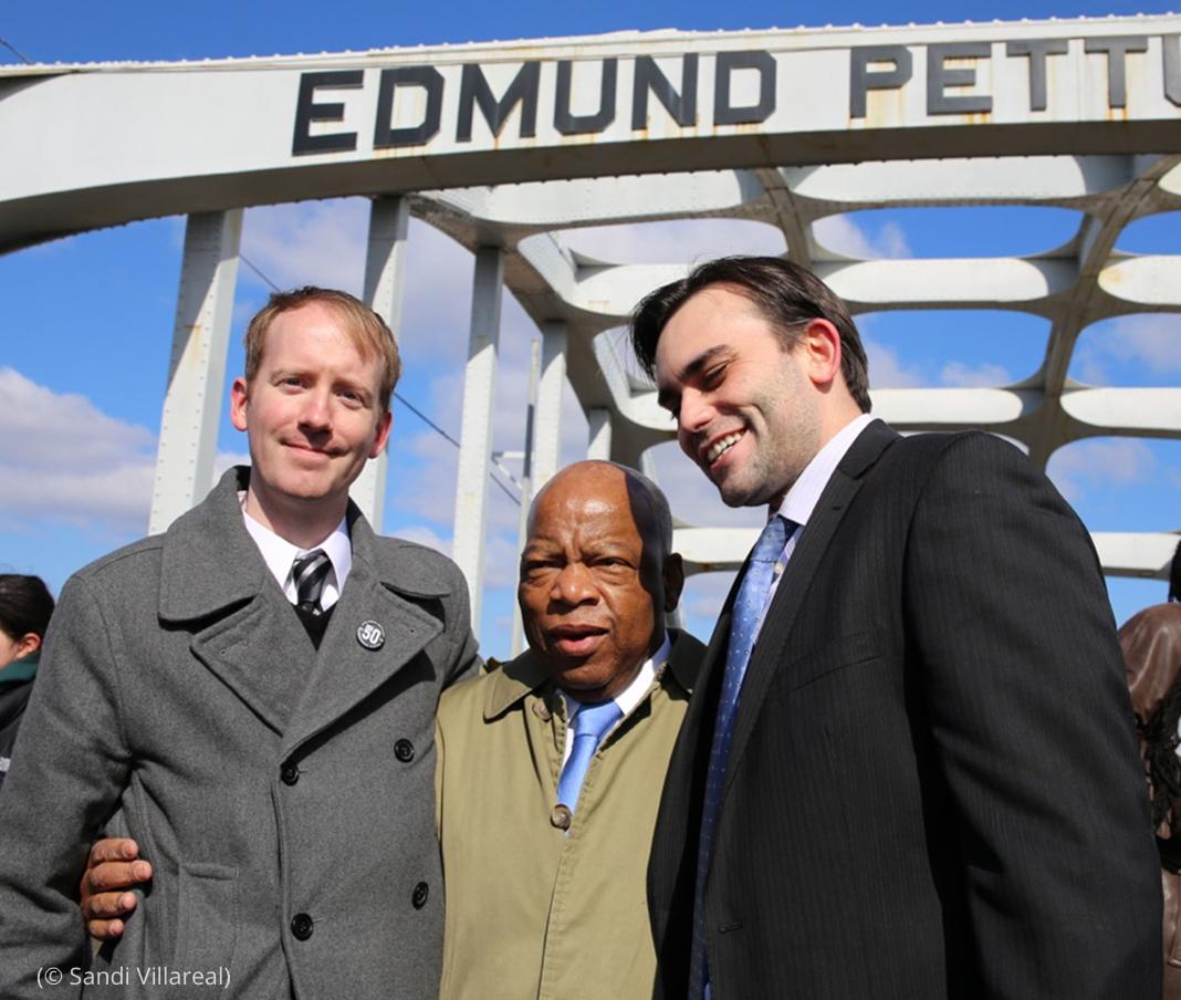 Trois hommes se tenant par la taille, posant en photo sur un pont (© Sandi Villareal)