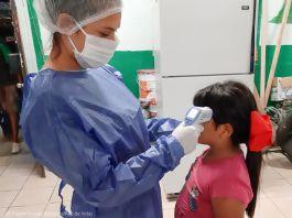 Mulher com equipamento de proteção mede a temperatura de uma menina (© Pastor Ismael Martinez/Pan de Vida)