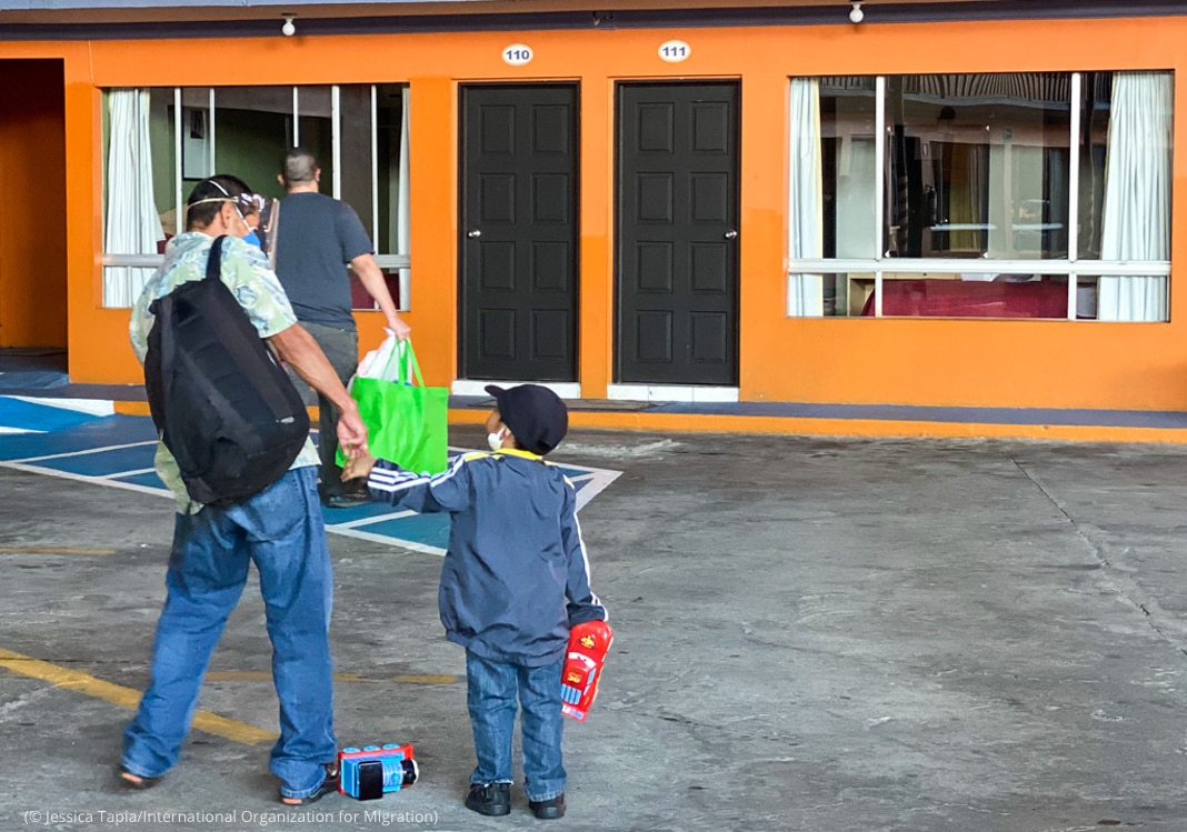 Man holding boy's hand and walking toward building (© Jessica Tapia/International Organization for Migration)
