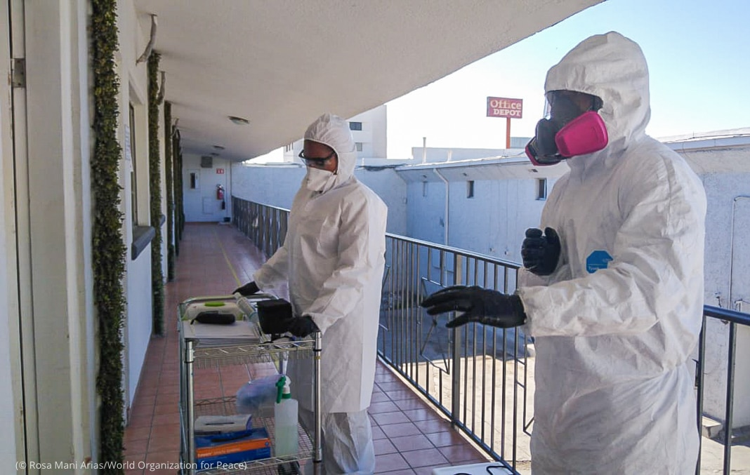 Two people in protective gear standing at motel room door (© Rosa Mani Arias/World Organization for Peace)
