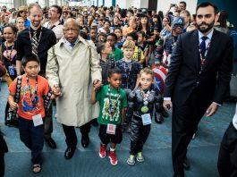 John Lewis de mãos dadas com crianças, conduz outras pessoas em marcha por um corredor (© Carlos Gonzalez/The New York Times)
