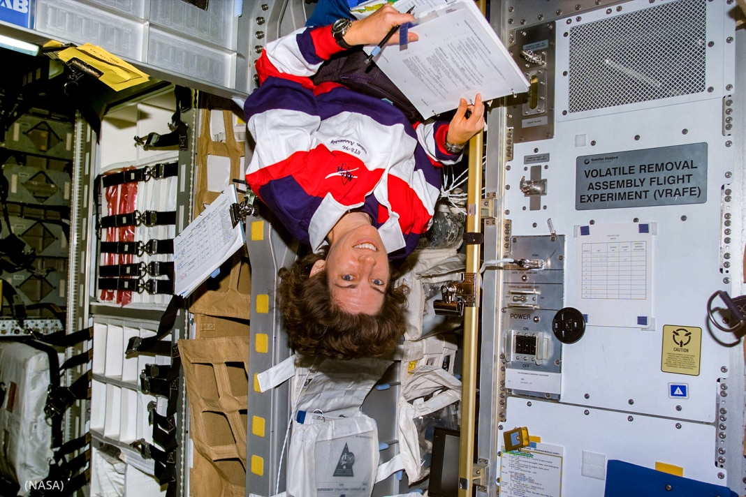 Woman floating upside down in space shuttle (NASA)