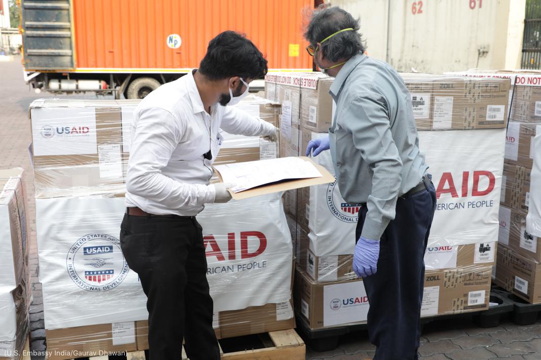 "Two men pointing at boxes marked ""USAID"" (U.S. Embassy India/Gaurav Dhawan)"