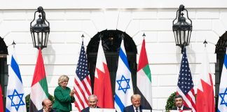 Le président Trump et trois hommes assis à une table devant la Maison Blanche avec une rangée de drapeaux derrière eux et une femme debout en train d'applaudir (Maison Blanche/Shealah Craighead)