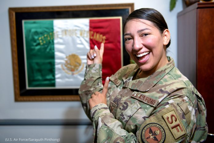 Woman in uniform pointing to Mexican flag and smiling (U.S. Air Force/Sarayuth Pinthong)
