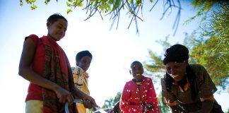 چار عورتیں پلاسٹک کے گیلنوں میں پائپ کے ذریعے پانی بھر رہی ہیں (USAID)