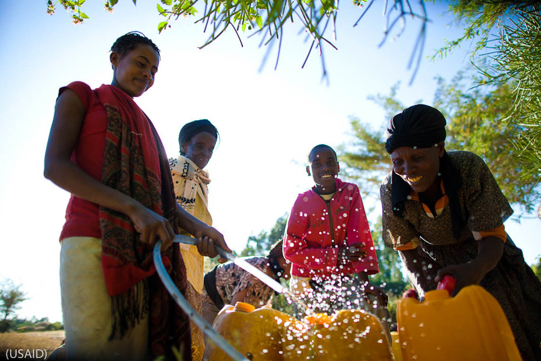 Four women filling plastic cans with water from hose (USAID)