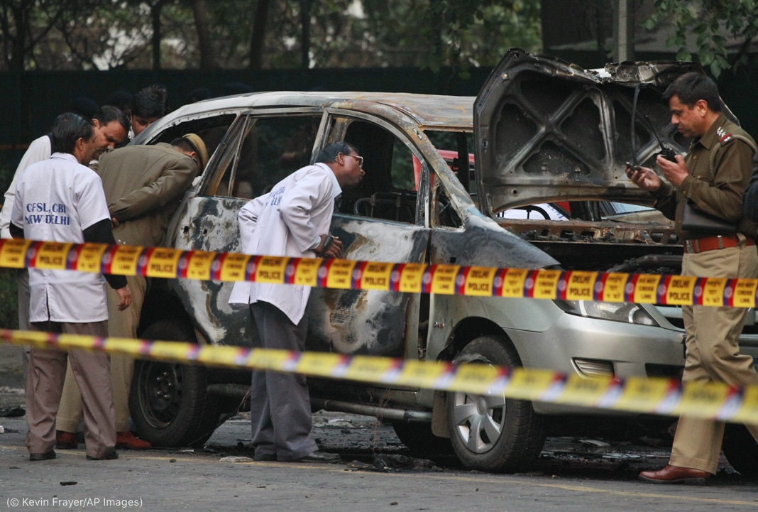 Men in white coats and others examining a car with bomb damage (© Kevin Frayer/AP Images)