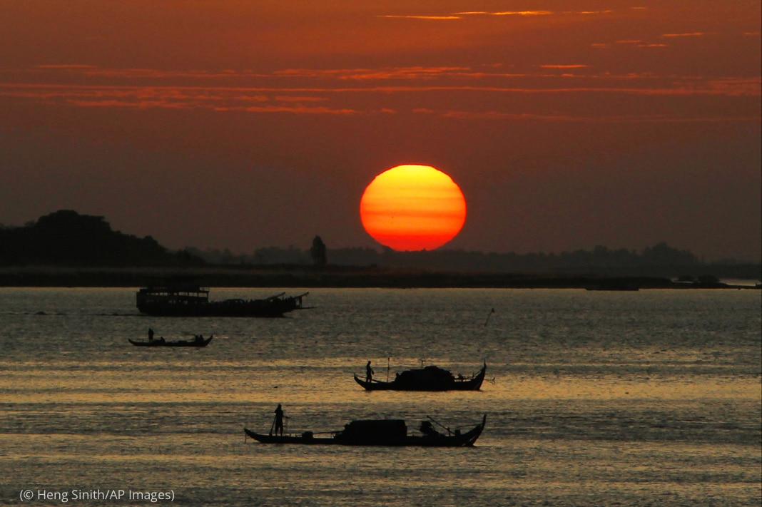 Sun setting behind fishing boats on Mekong River (© Heng Sinith/AP Images)