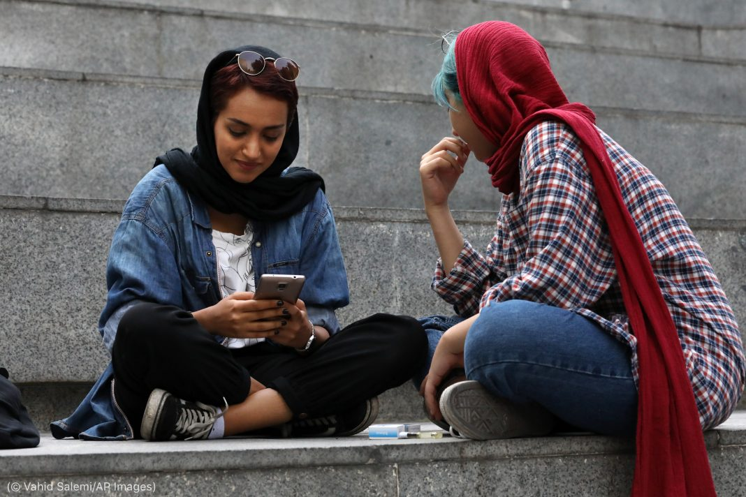 Two young Iranian women, one working on a cell phone (© Vahid Salemi/AP Images)