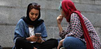 Dos mujeres mirando un teléfono móvil (© Vahid Salemi/AP Images)