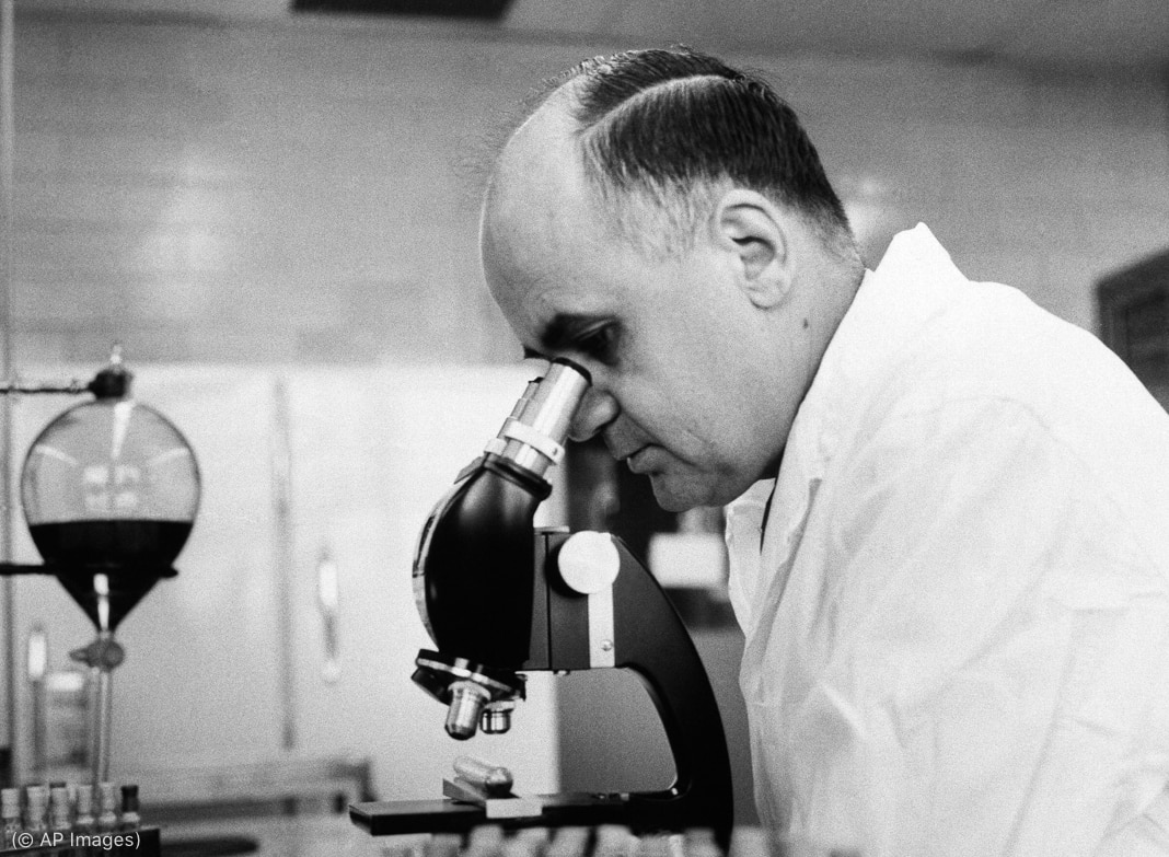 Scientist using microscope in laboratory (© AP Images)