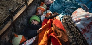 Children sleeping under blankets (© Felipe Dana/AP Images)