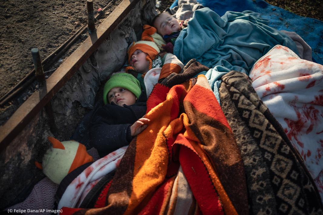 Children sleeping under blankets (© Felipe Dana/AP Images)