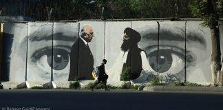 Menino caminha em frente a mural contendo a ilustração de dois homens de pé em frente à imagem dos olhos de uma pessoa (© Rahmat Gul/AP Images)