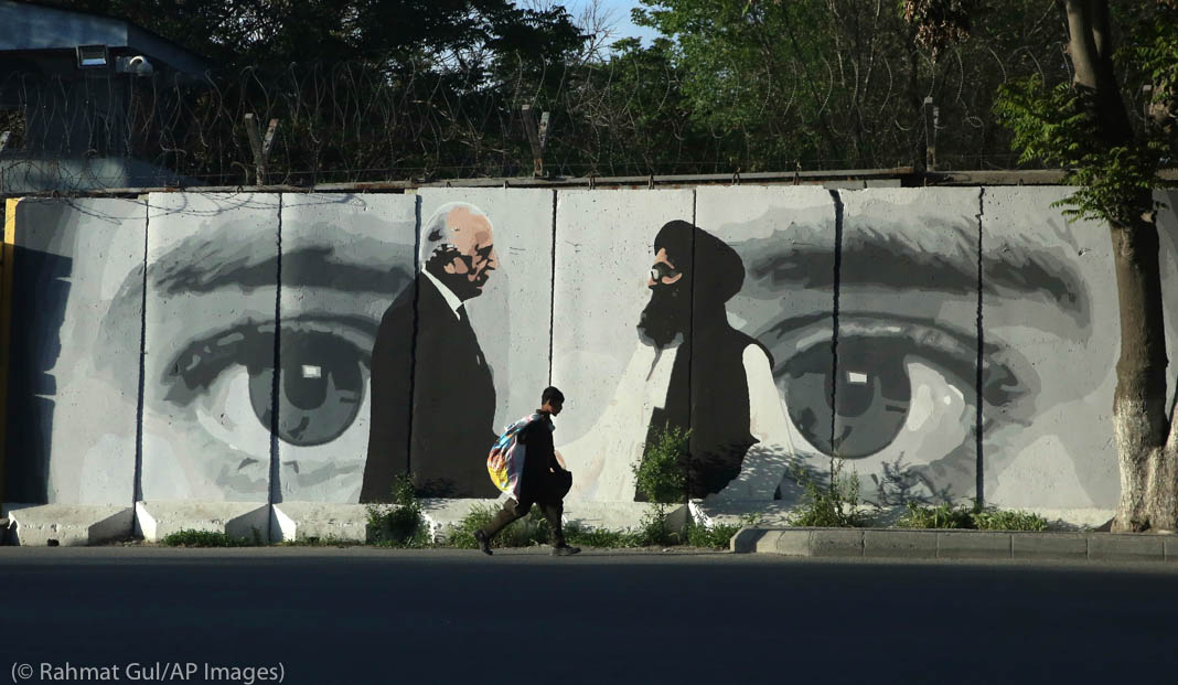 Boy walking in front of a mural of two men standing in front of a pair of eyes (© Rahmat Gul/AP Images)