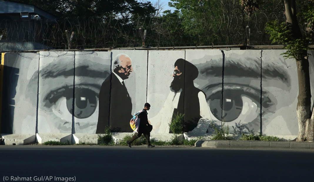 Niño caminando frente a un mural que muestra dos hombres parados frente a un par de ojos (© Rahmat Gul/AP Images)
