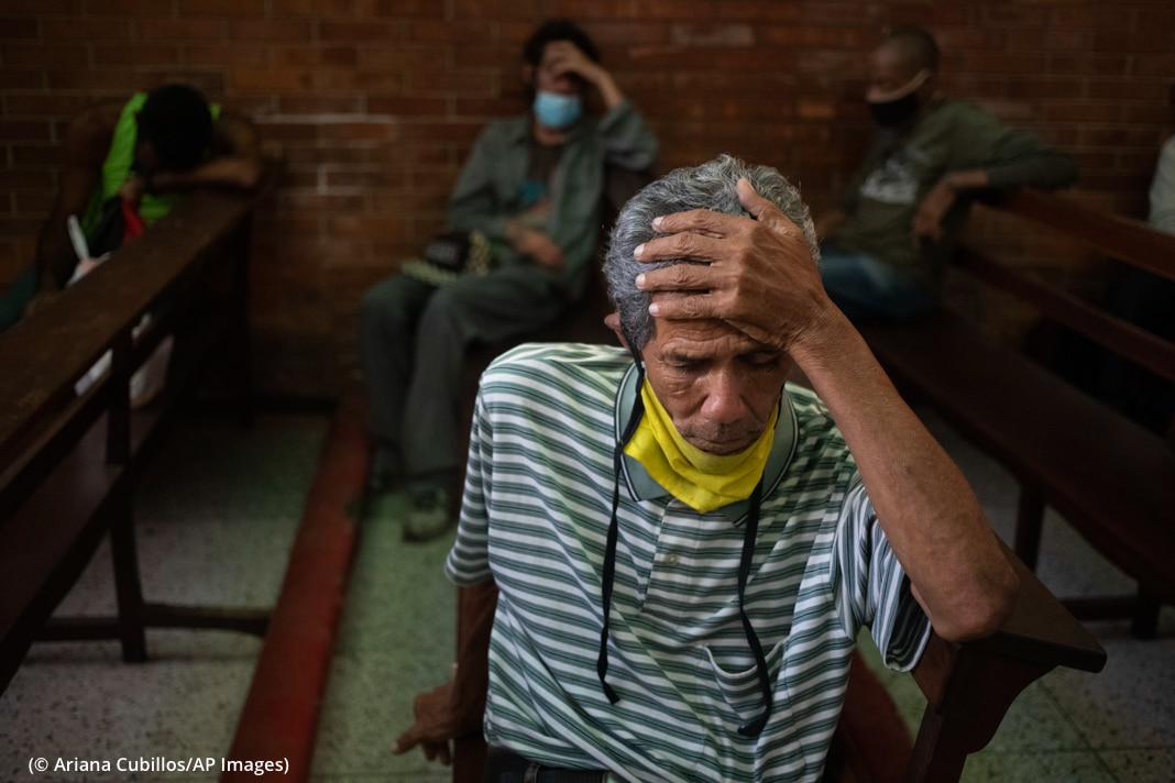 Man resting head in hand (© Ariana Cubillos/AP Images)