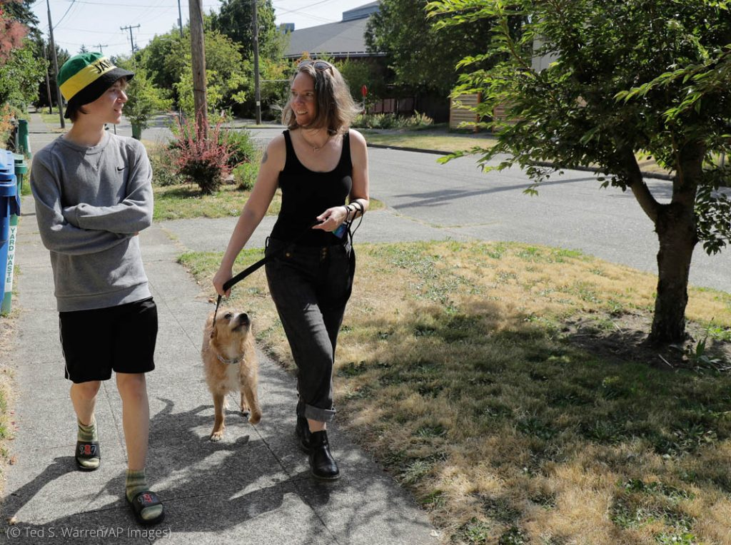 Two people walking on sidewalk, one holding dog on leash (© Ted S. Warren/AP Images)