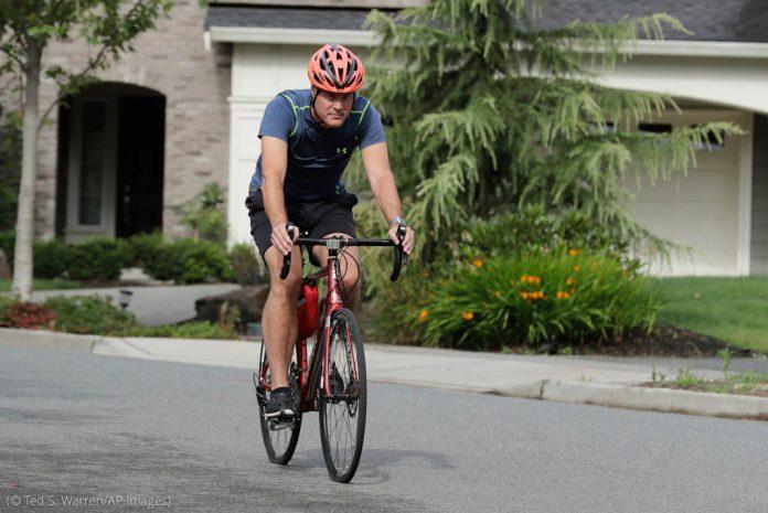 Man riding bicycle (© Ted S. Warren/AP Images)