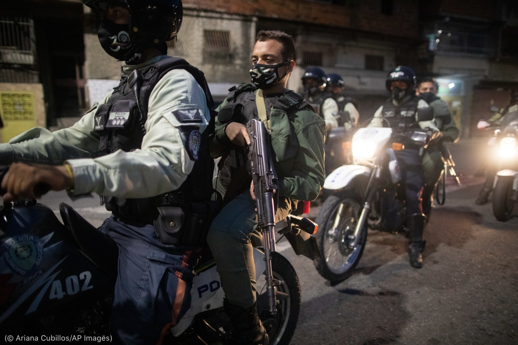 Soldiers and police officers riding on motorcycles while holding rifles (© Ariana Cubillos/AP Images)