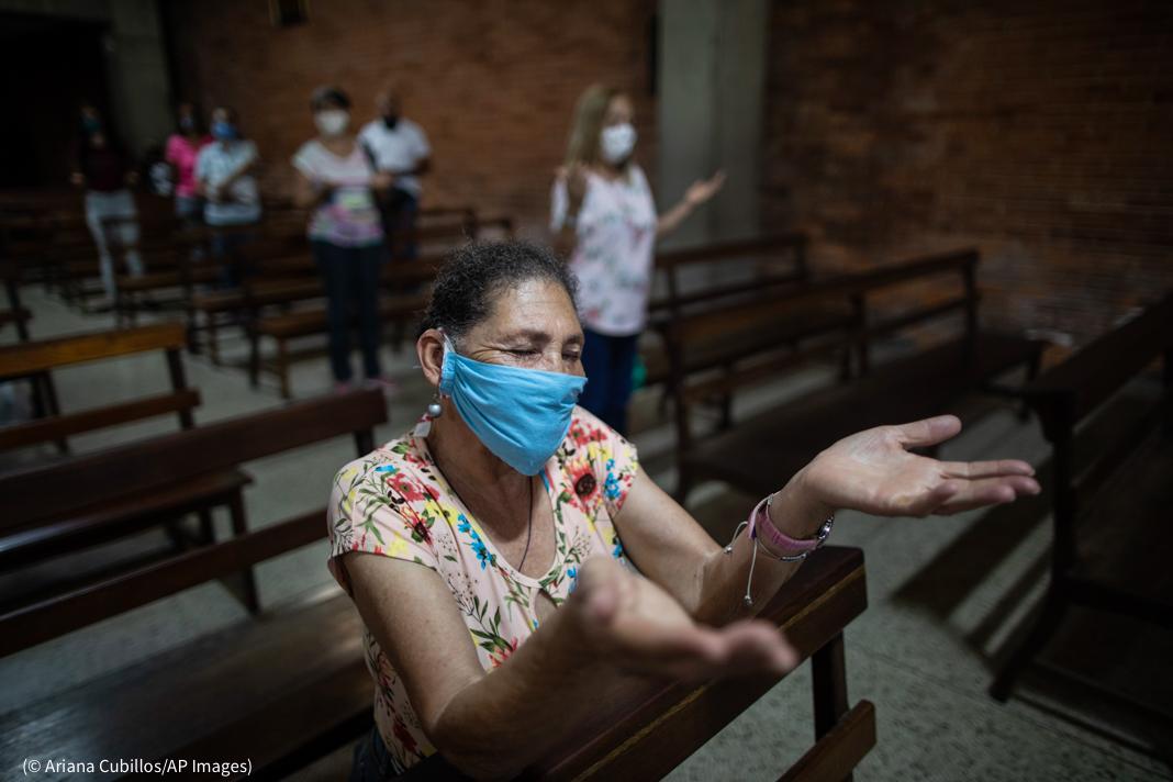Plan serré sur une femme agenouillée en train de prier dans une église, avec d'autres femmes en arrière-plan (© Ariana Cubillos/AP Images)