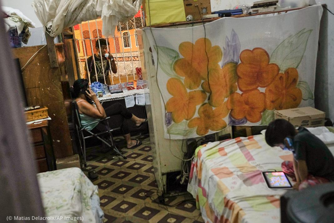 Dos personas en una ventana enrejada, niño por divisor de habitaciones mirando una tableta electrónica (© Matías Delacroix/AP Images)