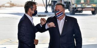 Two men wearing masks and tapping arms (© Aris Messinis/AP Images)