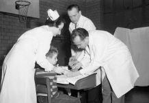 Un médecin en train de faire une piqûre dans le bras d'un petit garçon dans le gymnase d'une école, aidé de deux assistants médicaux (© AP Images)