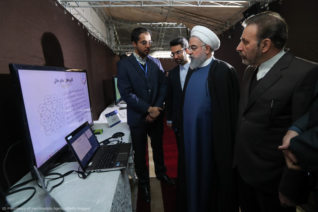 Hassan Rouhani and others looking at large monitor and laptop (© Presidency of Iran/Anadolu Agency/Getty Images)