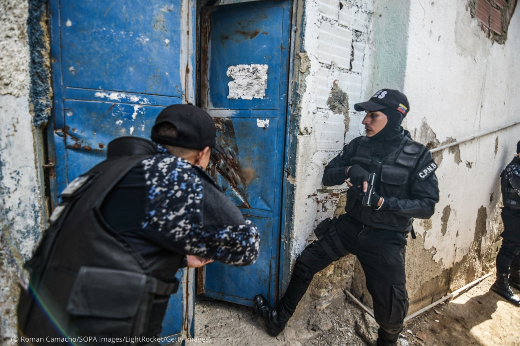 Two men in police uniforms preparing to enter doorway while holding weapons (© Roman Camacho/SOPA Images/LightRocket/Getty Images)