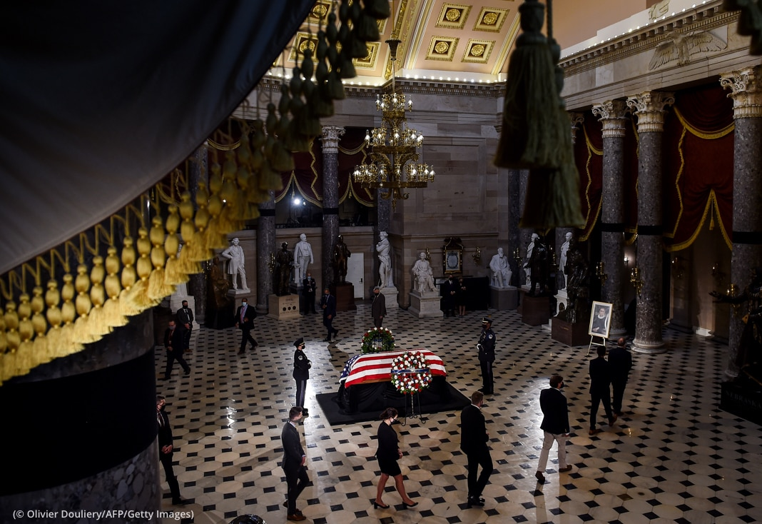 People around casket covered in U.S. flag in room with statues (© Olivier Douliery/AFP/Getty Images)