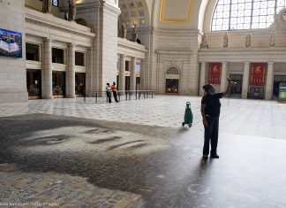 Woman taking photo with mural on floor in large hall of building (© Tasos Katopodis/Getty Images)